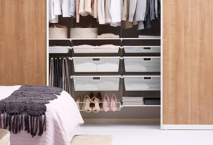 Elfa closet with wall mounted storage and slidng doors.