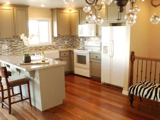 See This Transitional Kitchen With White Appliances Cream Cabinets And A Brown Mosaic Tile Backsplash