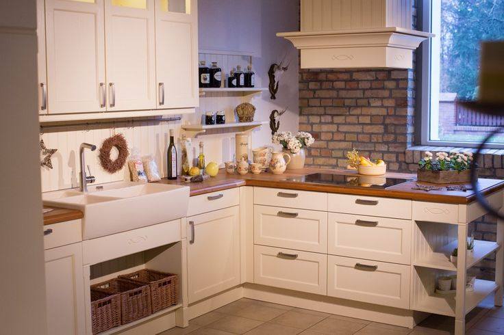 Landhausküche Bristol (lackierte Esche, Vanille). Keramikspüle und Weidenkörbe im Unterschrank, sowie ein Rückwandpaneel mit Nischen-Reling-System. Hersteller: Häcker Küchen