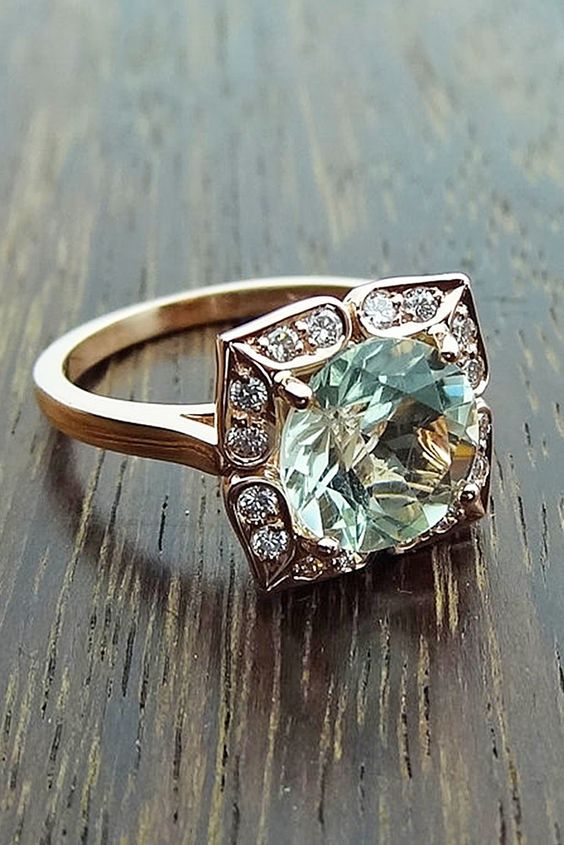 This rose gold, vintage green aquamarine engagement ring boasts a beautiful floral setting. Perfect for the nontraditional bride!