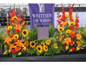 Article Tab: Flowers frame the podium for the Whittier Law School commencement.