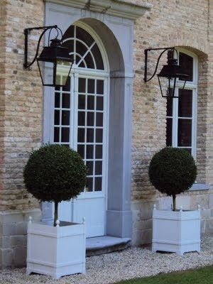 Buff brick, arched french door with blue cornice and framing, cantilevered black iron lanterns, boxwood topiaries in square planters.
