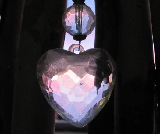 Romance discovered right in my patio corner...sunset's pink spills into this heart suspended against my rustic handmade screen