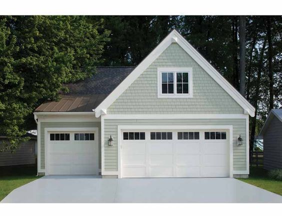 White carriage house style garage doors on a detached garage door. Can be constructed in wood or low-maintenance insulated steel. www.clopay.com: