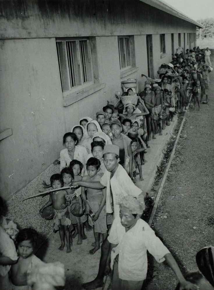 De vermagerde en uitgehongerde bevolking van Madoera staat twee maal daags in een lange rij bij een voedseluitdeling van het Rode Kruis, Indonesië na de eerste politionele actie, 20 augustus 1947.