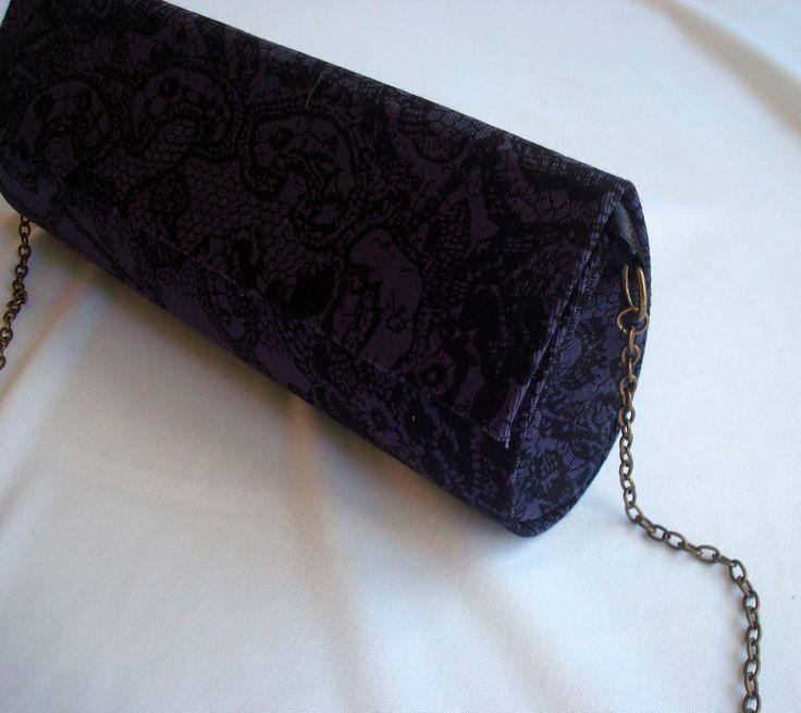 Bolsa de festa em tecido 100% algodão por dentro e por fora. <br> <br>Por fora tecido roxo escuro com estampa bordada. Clássica, uma ótima opção para substituir a velha bolsa preta! <br>Lateral no mesmo tecido. <br>Por dentro, em perfeita harmonia, tecido roxo um pouco mais vivo, com delicados poás brancos. <br>Com alça de corrente ouro velho, pode ser usada com ou sem alça. <br> <br>Dimensões: 20 x 10 x 6 cm