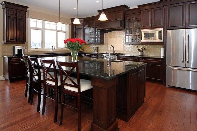 Hardwood floors, dark cabinets, granite counters, light tiled backdrop