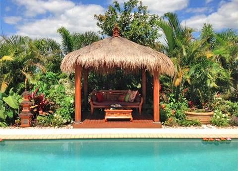 cool your backyard with a thatched roof gazebo bali hut beside a pool