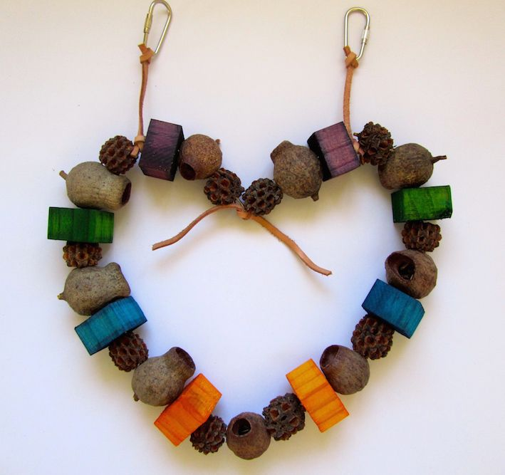 This parrot toy has been made in a gorgeous heart shape with a mixed assortment of Australian natural seeds and pods - large sized gumnuts, casuarina seeds, and natural pine biscuits - coloured with bird safe food dye.  Available from www.onestopparrotshop.com