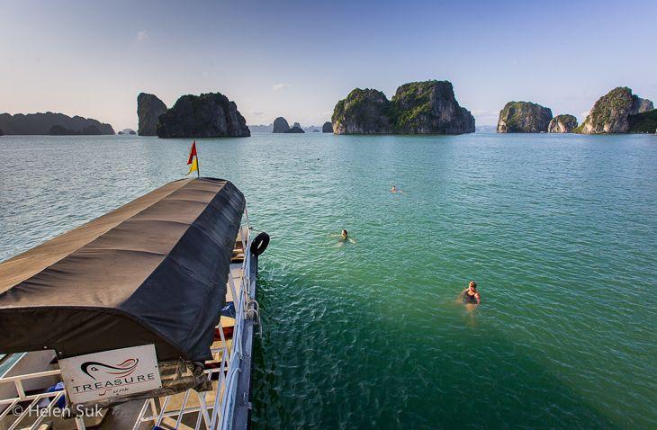 treasure junk, passengers swimming in the emerald waters of bai tu long bay vietnam