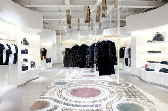 """Versace has opened up a new concept store in SoHo, New York, which is the brainchild of Donatella Versace and English architect Jamie Fobert. The building spanning to 1,785-square-foot itself is reminiscent of a fashion show runway, and has been described as opening """"onto a long corridor lined with six white and gold rotating panels"""". The mosaic flooring make you feel like you are in an 800BC Roman basilica with a modern touch of """"contrasting wavy plexiglass panels hanging from above""""…"""