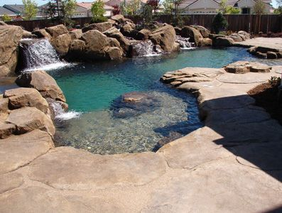Beautifully designed lagoon pool with sculpted boulders and rock edging. This would be incredible with a green backdrop...