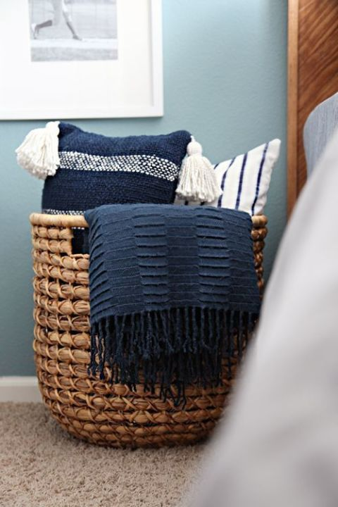 A wicker catch-all adds a rustic touch to a bedroom and creates an instant way to store pillows with ease. If you get one that's big enough, you can add throw blankets to the basket as well. Click through for more on this and other bedroom throw pillow storage ideas.