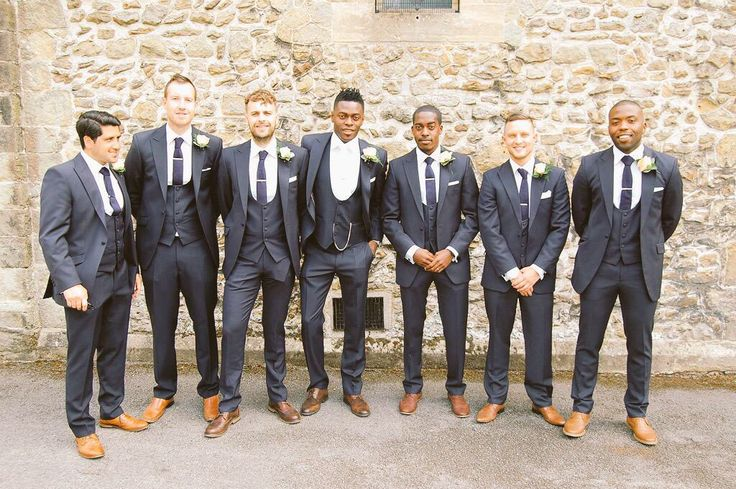 Groom and ushers in navy blue slim fit suits with scoop waistcoats and brown shoes. The wedding suit.