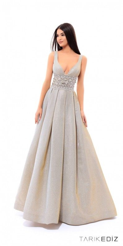Glisten and shine like a sparkling diamond in this Cindrella Evening Dress by Tarik Ediz. This gorgeous dress features a plunging V-shape neckline, a box pleated glitter A-line silhouette, and an embellished waistband with a bow tie. #edressme