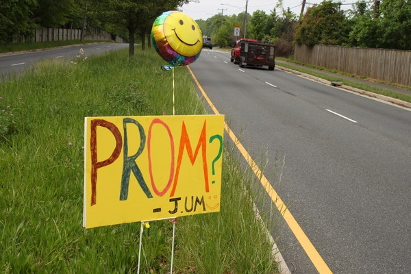 A Lake Braddock student sets signs in the median asking a girl to prom.