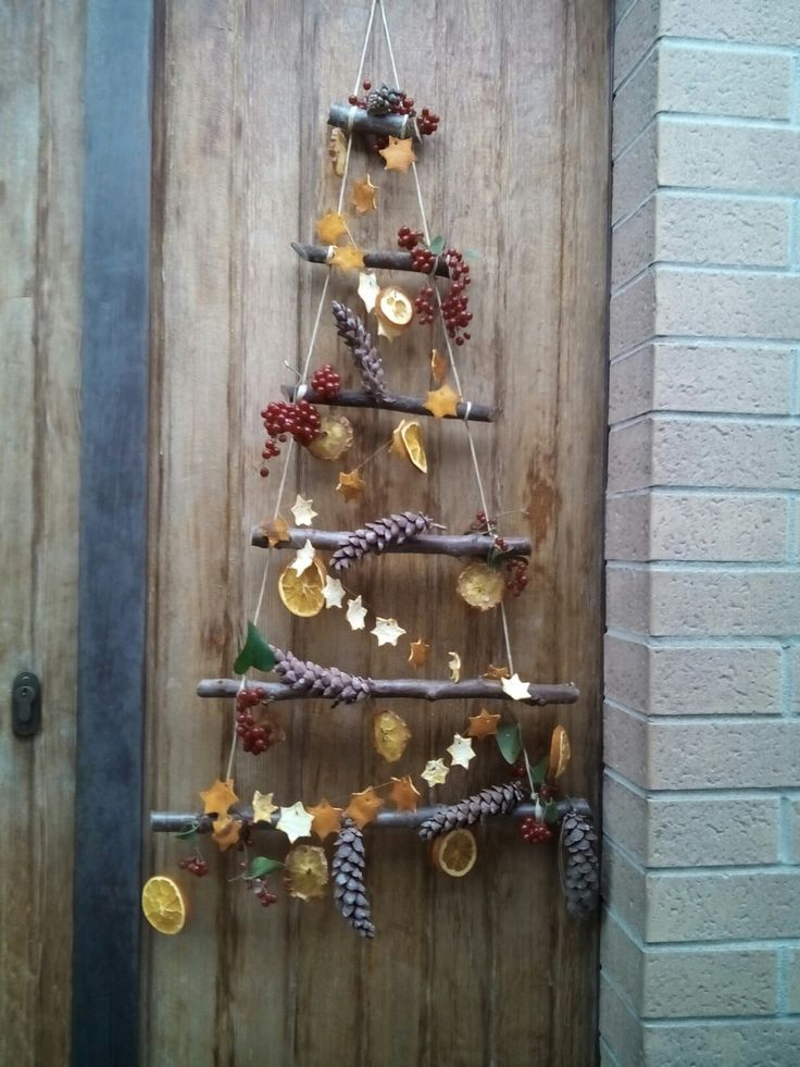 Addobbi natalizi. Alberello con legnetti, arance,mele essiccate, pigne e bacche del bosco.