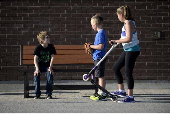 """Owen Stewart, left, Ben Irvine, second from right, and Abby Irvine, right, shown with 'buddy bench' at Rick Hansen Public School in Aurora, Ontario on Wednesday. Owen, 9, has changed school three times in six years. He's been lonely at his last schools, but he's made friends at Rick Hansen thanks to the """"buddy bench."""""""
