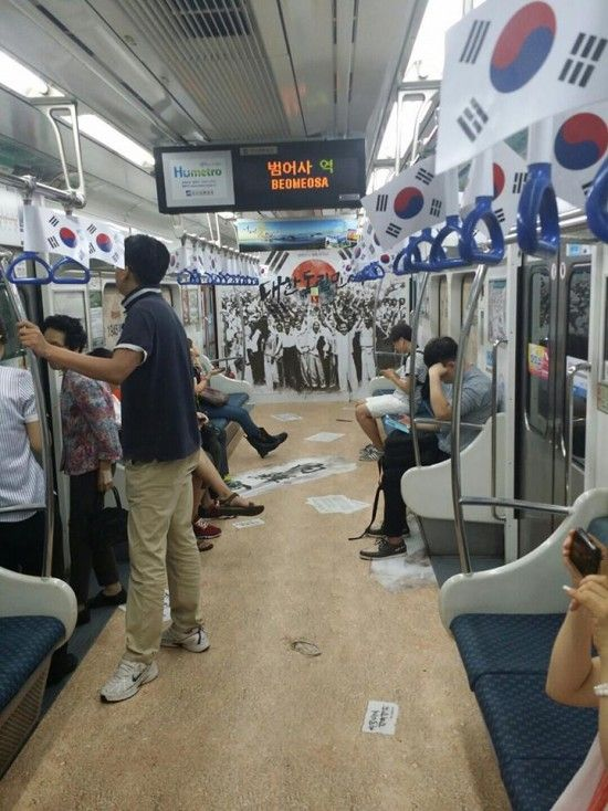 """August 15 is Korea's Independence Day (Gwangbokjeol). On this day, Koreans are encouraged to display the Korean flag, from their homes, stores, public establishments. This subway line in Busan went all out with its Korean pride, as subway riders were surprised to find not only mini-flags dangling from the ceiling, but a huge poster of the cheering nation, informative posters on the history of Independence Day, as well as decorated doors to create a """"Reply 1945 Busan"""" themed ride."""
