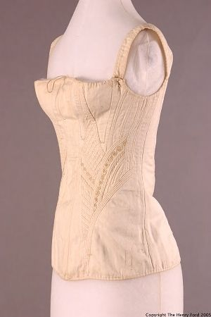 1838-1840   White cotton sateen quilted corset with needle running in channels. Four gussets in center front, breast high on the torso. Channel for busk in center front, open at center back for insertion and removal. Busk held in place with pins, holes are visible where pins were used. Drawstring around the top edge of the corset. Candle wicking in channels, or needle run, forms the structure- a stiffening that pulls the body up and in. Decorative silk embroidery.