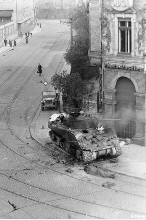 An M4 tank burns at the intersection of Karl Heine Str. and Zschochersche Str. in Leipzig, Germany, near the end of the war in Europe, 18 April 1945.