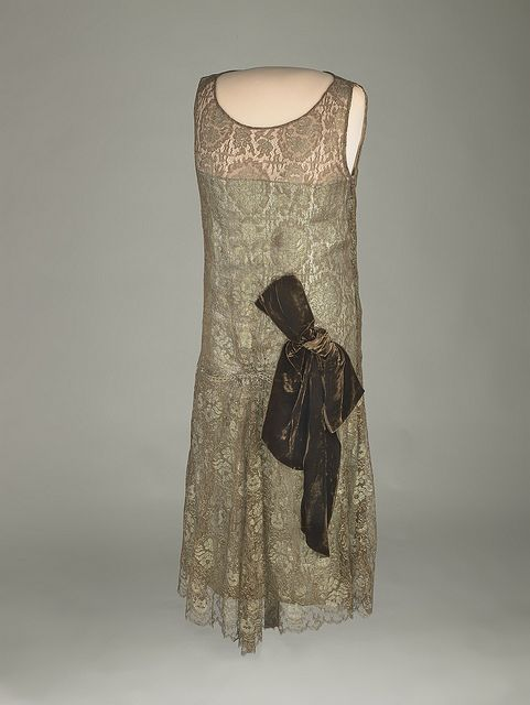 Grace Coolidge's Lace Dress. Brown chiffon and lace flapper-style dress trimmed with metallic thread and a brown velvet bow. Grace Coolidge gave the dress to her White House maid, Maggie Rogers. It was likely shortened to be worn by Maggie's daughter Lillian.