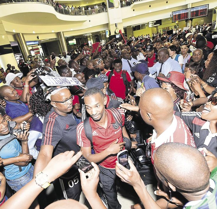 BOSASA RMS Directors Sylvester Simelane and Stoffel Mosehle tries to get Orlando Pirates players through the crowd at O.R International Airport. The Orlando Pirates fans filled the airport waiting to cheer for their team after they win 4-3 against Al Ahly in the CAF Confederation Cup.