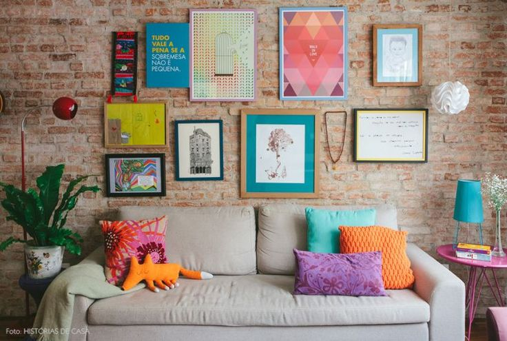 An eclectic wall gallery with a brick wall in the background... marrying the industrial look with a bit of whimsey