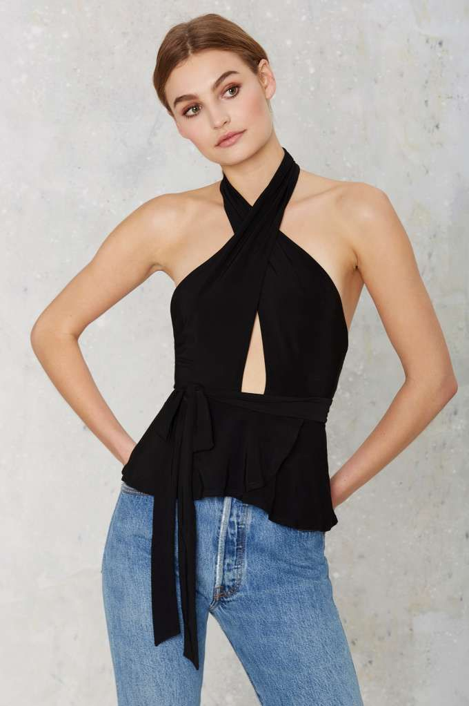The Cruel to be Kind Top is black and features a halter neck with crossover design, cutout at center, peplum, and tie at waist.