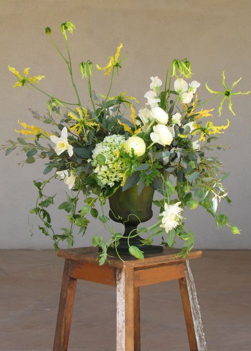 centerpiece with ivory sweet peas, ivory ranunculus, ivory daffodils, yellow gloriosa lily, green hydrangea, scented geranium, gunnii eucalyptus, and passion vine, arranged in a vintage green glass urn