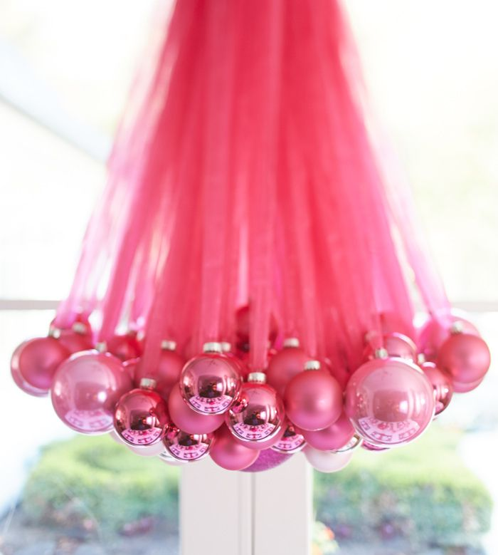 Create a gorgeous DIY chandelier for your guests to gush over using ornaments in all different sizes  and ribbon. | Setting the holiday table: Canterberry Magenta
