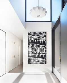 An entryway with a eclectic pendant light, graphic monochrome art, and high ceilings