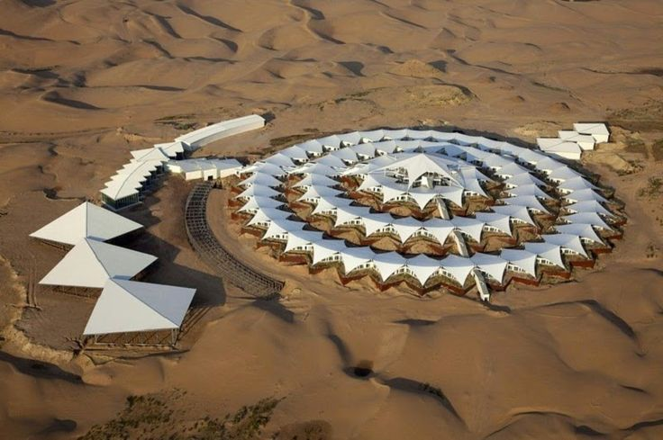 Located in Inner Mongolia, the Desert Lotus Hotel's structure consist of repeating triangular white tent tops, rotated 45 degrees and connected together in a circular formation like a lotus, hence it's name.