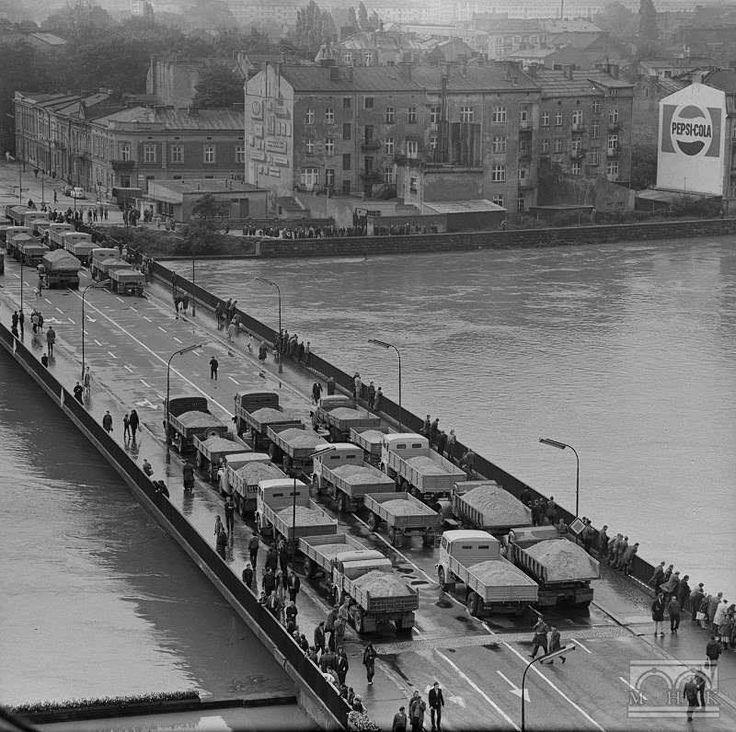 """Powódź 1972 roku. Ujęcie z DH """"Jubilat"""" na Most Dębnicki, na którym stoją ciężarówki załadowane piaskiem w celu dociążenia konstrukcji."""