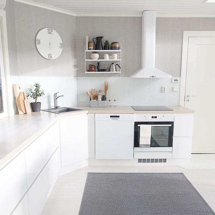 Harmaa väri tasapainottaa keittiön valkoista ilmettä. Yksityiskohtia tilaan tuo seinäkello, String Pocket hylly sekä kodikas matto.