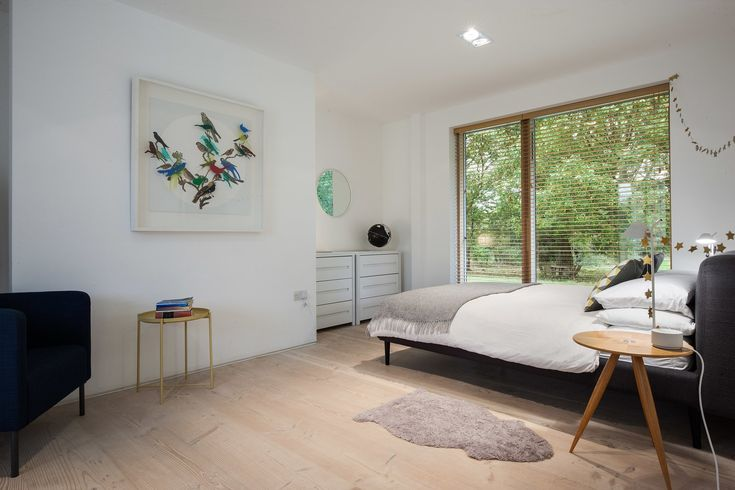 Tagged: Bedroom, Bed, Chair, Light Hardwood Floor, Night Stands, Dresser, and Recessed Lighting.  Photo 5 of 182 in Best Bedroom Ceiling Photos from A Scandinavian-Style Pavilion in England Is Listed For $2.1M