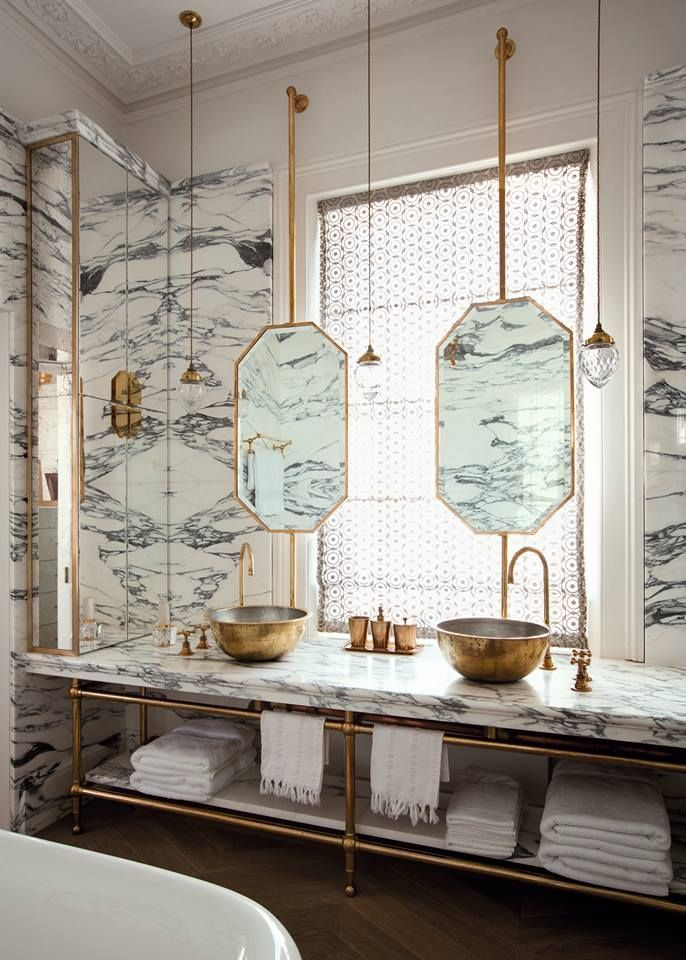 Here's a space-saving style tip: Hang mirrors in front of the window if you're lacking the wall space. You'll create a stunning effect like this one by Maddux Creative AND you'll get the best light for doing your makeup! #interiordesign #bathroomdesign #spacesavers #stylingtips