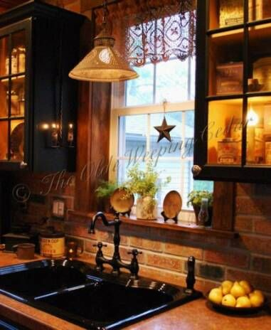 Have painted my cupboards black... would love a reclaimed brick backsplash, but wonder how impossible it would be to clean near the stove? (grease) Wouldn't a sealant make the brick shiny?  PS... love the glass doors with tiny lamps behind as well... too pretty!