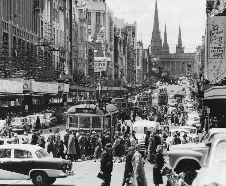 A bustling Bourke St, Melbourne surrounded with an array of Christmas decorations in 1957. Fairfax Archives.