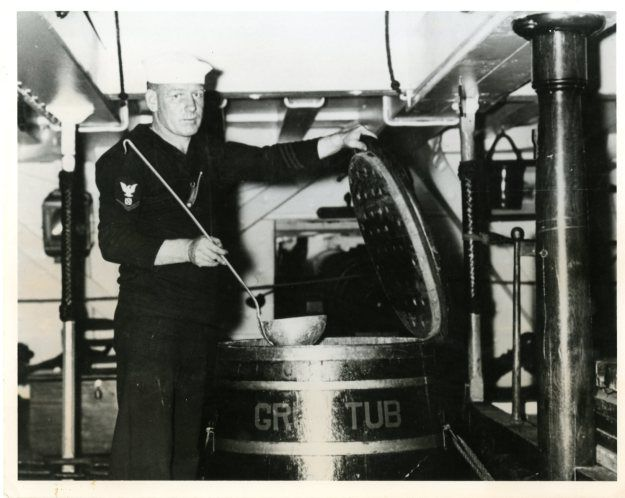 "A sailor displays the old ""Grog Tub"" on USS Constitution in the 1930s"