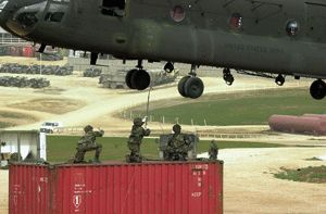 A soldier reaches up to touch a CH-47 Chinook helicopter as he and his fellow soldiers prepare to sling load a container from Camp Bondsteel