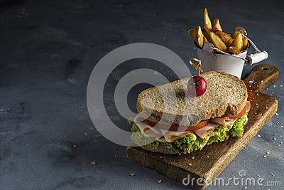 Turkey sandwich with lettuce and tomatoes  on a wooden board and chips within a small bucket.