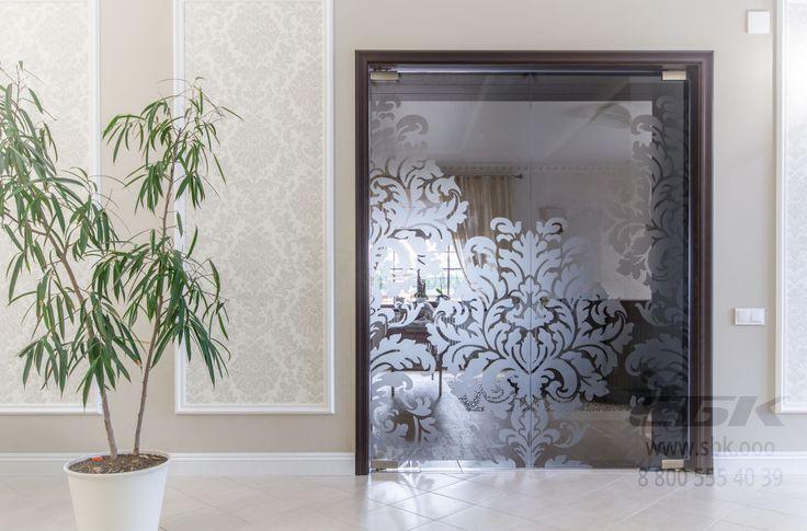 Маятниковая двустворчатая дверь из закаленного стекла с пескоструйной обработкой и хрустальными ручками.