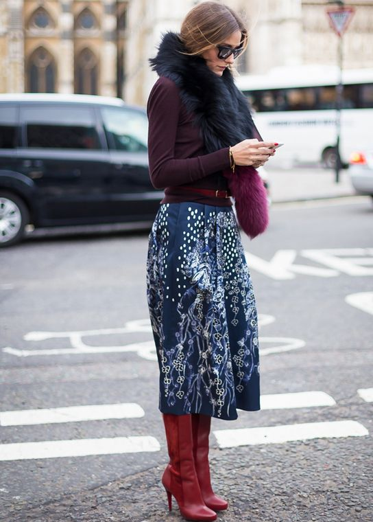 Olivia Palermo wearing a two-toned scarf, printed bottoms, and red tall boots
