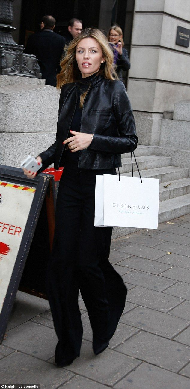 Strutting her stuff: The beauty carried a Debenhams bag over one arm and her phone in the ...