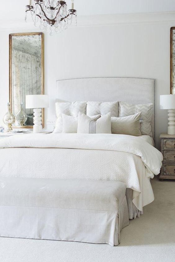 Wonderful French Transitional Bedroom Features A Pale Gray Nailhead Headboard    Mirrors On Both Side    On Bed Dressed In White Chevron Pillows Flanked By  French Wood ...