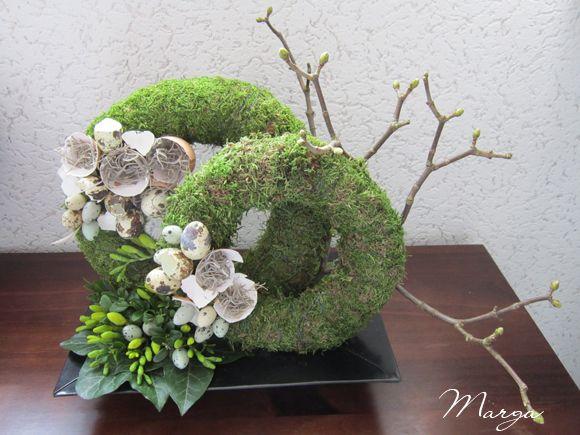 Twee kransen met mos bekleden, en paasdecoratie. Rechts een tak plaatsen, en verder afwerken met, klimopblad, Buxus, en fresia's.