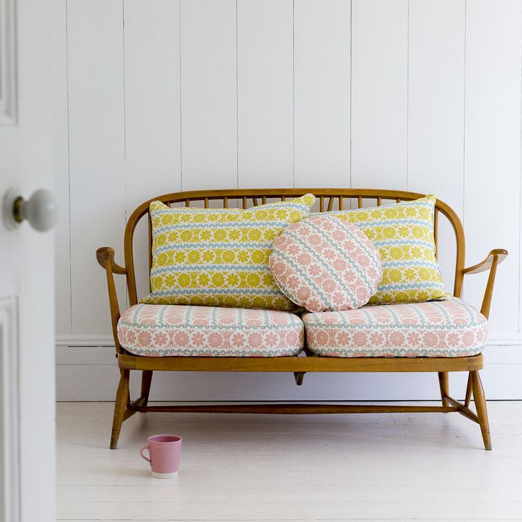 Pink and yellow sofa cushions on a retro wooden sofa | St Judes fabrics