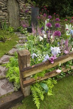 Stone garden Walk path with lush flower garden and stone shed, with lawn grass, irises, allium, in pink, lavender and blue color theme tones in late spring bloom
