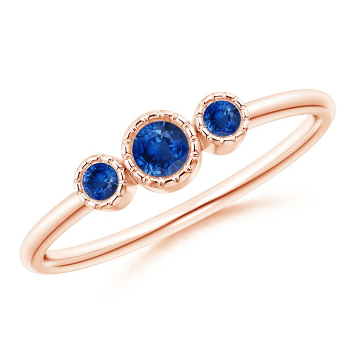This trio stone pattern ring features a mesmerizing sapphire, flanked by two smaller round sapphires. They are secured in a bezel setting and are rimmed with intricate cutwork for a unique look. Designed in 14k rose gold, this blue sapphire stackable ring is an everlasting symbol of your past, present and future.